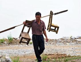 石兰松送完孩子用船桨挑着小板凳回家